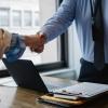 crop colleagues shaking hands in office